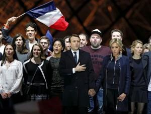 """Foto """"L'Express"""", text """"Justițiarul"""": Emmanuel Macron, președintele ales, alături de soția sa, Brigitte Trogneux, pe esplanada muzeului Luvru, 7 mai 2017. Gestul """"patriotic"""" îl vedeți permanent și la Klaus Iohannis, altă creație a finanței mondiale."""